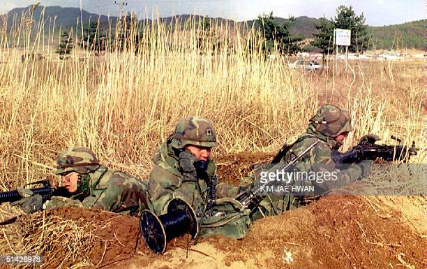 US soldier telephones his unit while on duty in a trench 25 March 1994 near the Demilitarzed Zone dividing the Korean peninsula as a crisis grows...