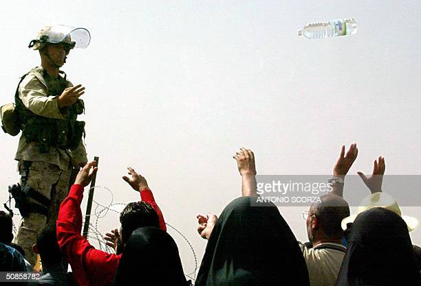 US soldier throws a bottle of mineral water to Iraqi people as they wait at the entrance of the Abu Ghraib prison 30 kms west of Baghdad 20 May 2004...