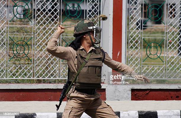 A soldier throws a rock using a slingshot at the protesters after violent protests broke out when thousand of People offered Eid prayers in Downtown...