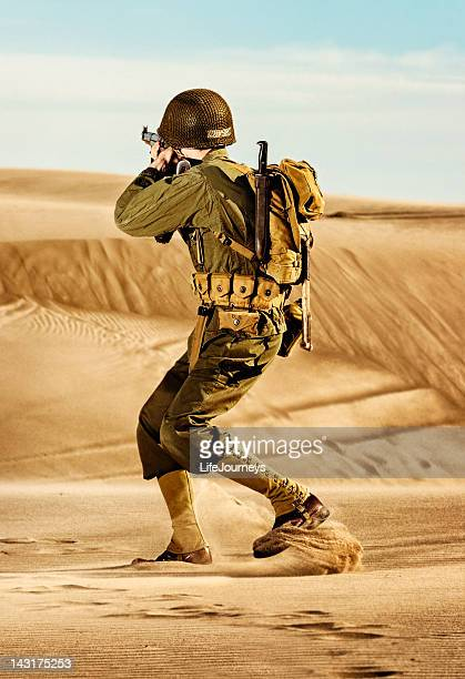 wwii soldier turning to fire his weapon - desert sands - boots rifle helmet stock pictures, royalty-free photos & images
