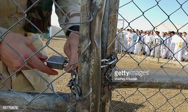 S soldier unlocks a gate as Iraqi detainees stand in line to be processed for release from Abu Ghraib prison facility on September 26 2005 in Abu...