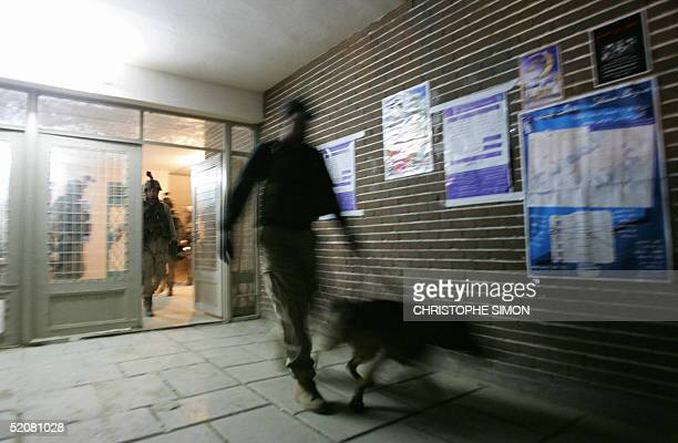 US soldier use a sniffer dog as he leads him into a polling station ready for tomorrow morning's national elections in the Sheikh Maatuf district in...
