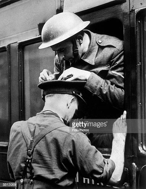 A soldier uses a comrade's hat to lean on to write a telegram home