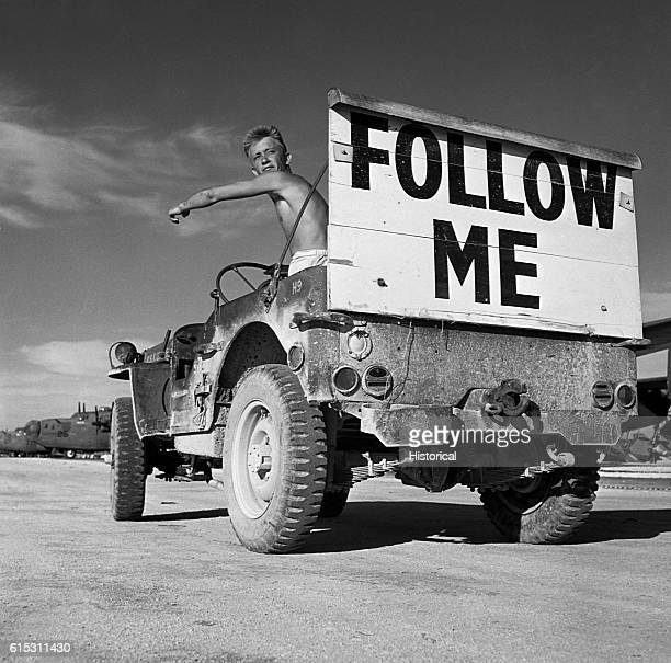 A soldier uses a jeep with a billboard reading 'Follow Me' to lead bombers to parking places on an Eniwetok airstrip B24 Liberator heavy bombers are...