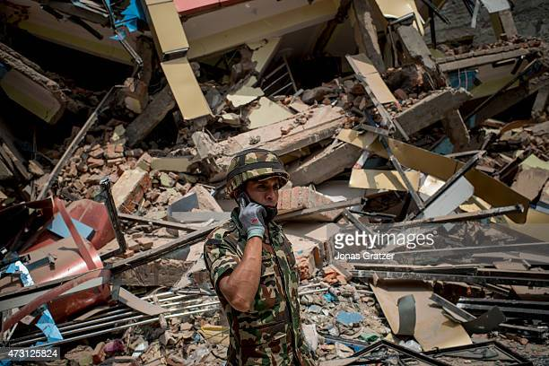 A soldier uses a mobile next to rubble following yesterday's earthquake on May 13 2015 in Kathmandu Nepal A 73 magnitude earthquake struck in Nepal...