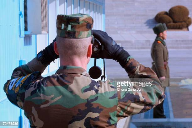 S soldier uses a pair of binoculars as he looks to the North as a North Korean soldier stands guard February 5 2003 at the truce village of Panmunjom...