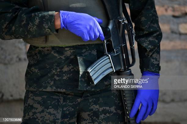 A soldier uses gloves as a precautionary measure against the spread of the new coronavirus COVID19 during an operation with Health personnel at the...