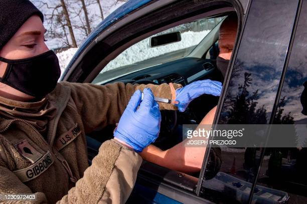 Soldier vaccinates a man in his car at a vaccination center in Londonderry, New Hampshire on February 4, 2021. - The drive-through center is run by...