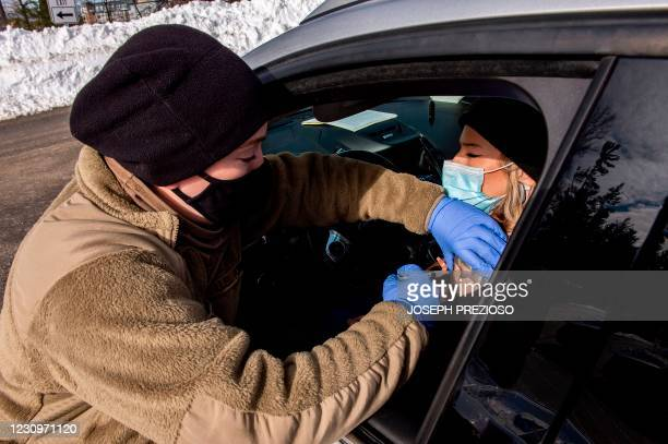 Soldier vaccinates a woman in her car at a vaccination center in Londonderry, New Hampshire on February 4, 2021. - The drive-through center is run by...