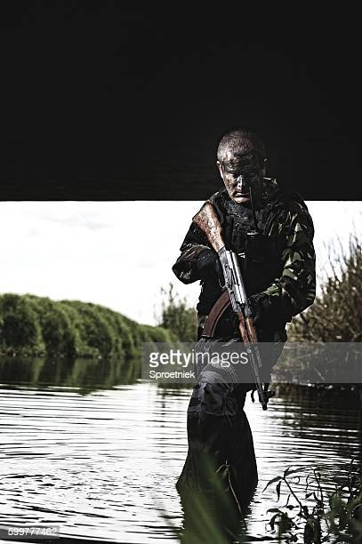 Soldier wades through deep water under a bridge