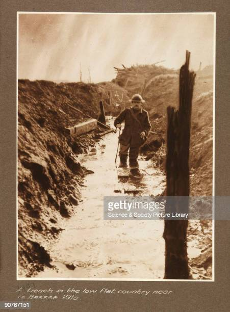 Soldier wading through a waterfilled trench taken by an unknown photographer in about 1917 during World War One The full caption reads 'A trench in...