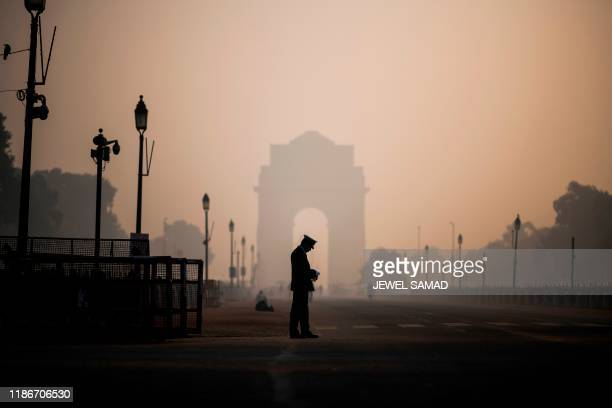 A soldier waits on a street near India Gate in heavy smoggy conditions in New Delhi on December 6 2019