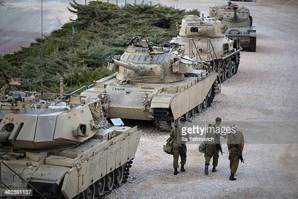 Soldier walk by a display of old tanks at the Latrun museum after a military ceremony for late former Prime Minister Ariel Sharon on January 13 2014...