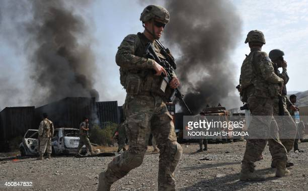 US soldier walk past burning trucks at the scene of a suicide attack at the AfghanPakistan border crossing in Torkham Nangarhar province on June 19...