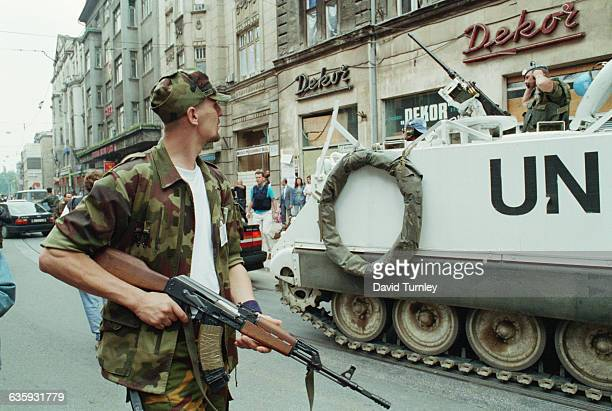 Soldier Walking by UN Personnel Carrier