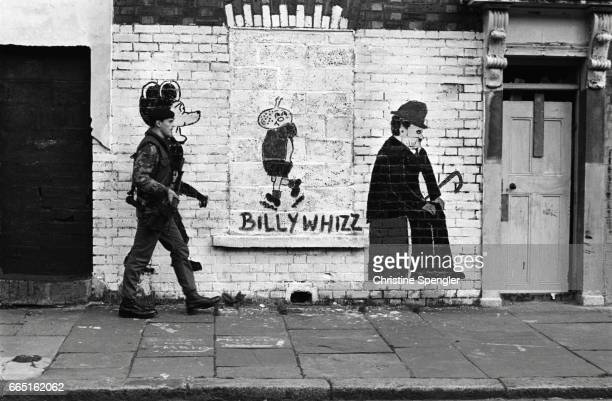 Soldier walking down Falls Road in Belfast merges into a picture of Mickey Mouse on a wall next to drawings of cartoon character Billy Whizz and...
