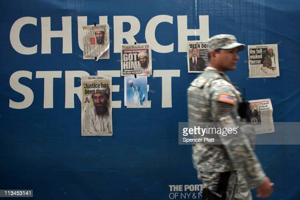 S soldier walks by newspaper clippings on a wall at Ground Zero heralding the death of Osama Bin Laden on May 2 2011 in New York City President...