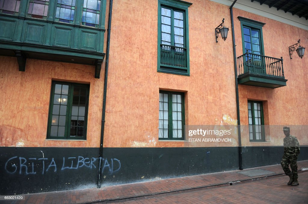 A soldier walks down a street in the historic neighborhood of La Candelaria in Bogota on September 17, 2009. La Candelaria is Bogota's oldest neighbourhood and the city's historical center, known for its colonial houses with wooden balconies and clay shingle roofs. AFP PHOTO/Eitan Abramovich /