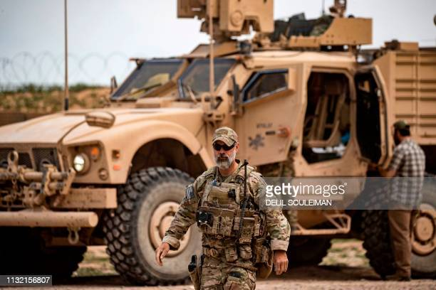 Soldier walks in front of a military vehicle near Omar oil field in the eastern Syrian Deir Ezzor province on March 23 after US-backed Syrian...