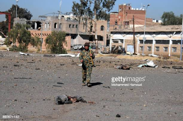 A soldier walks near a body of a prisoner after he was killed in airstrikes targeted the prison on December 13 2017 in Sana'a Yemen More than 12...
