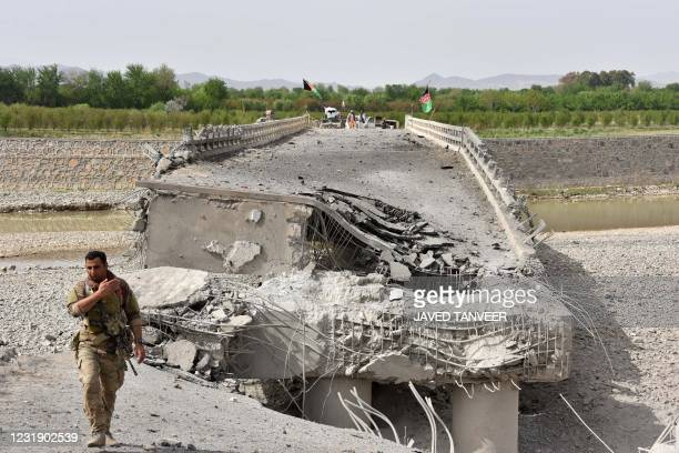 Soldier walks near the destroyed section of a bridge connecting Kandahar city and Arghandab district, near Kandahar on March 24, 2021 after a bomb...