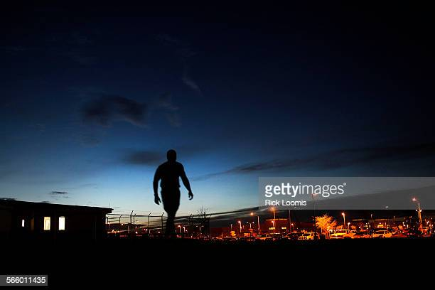 Soldier walks on base in the early morning hours when many of the troops perform personal training exercises. More than 349 U.S. Service members...