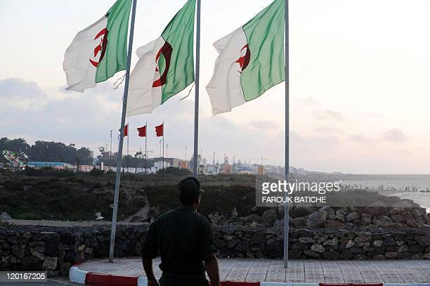 A soldier walks on the Algerian side of the AlgeriaMorocco border as Algerian flags sway in the wind near Tlemcen at a border post in the Marsat Ben...