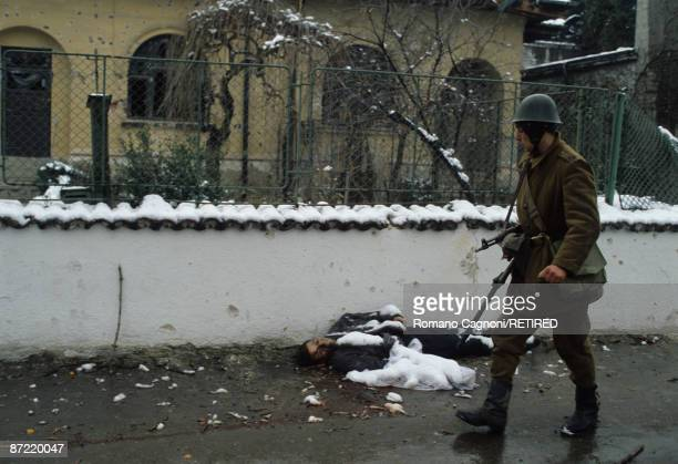 A soldier walks past a dead man lying in the street in Bucharest during the Romanian Revolution December 1989
