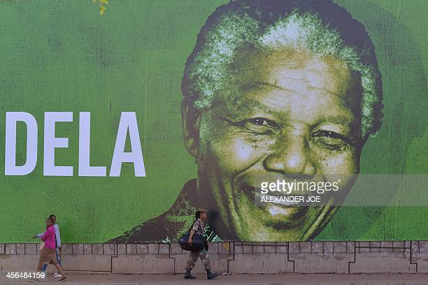 A soldier walks past a giant banner of South African former president Nelson Mandela on December 14 2013 in Pretoria Nelson Mandela will embark on...