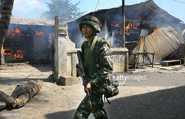A soldier walks past a house torched by gangs of youths in the Komoro district of the East Timorese capital Dili Street fighting has broken out and...