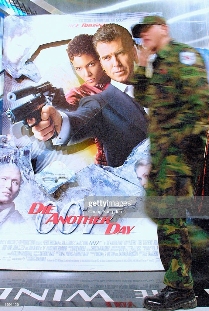 a soldier walks past a poster of the latest james bond movie die another