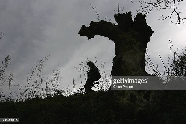 A soldier walks past a stump at a village on March 17 2006 in Panwa Kachin State Special Region 1 of Kachin State Myanmar The Kachin State Special...
