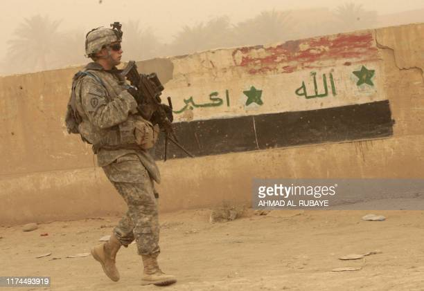 A US soldier walks past a wall painted in the Iraqi national colours during the last joint USIraq patrol in Khan Bani Saad some 10 kms south of the...