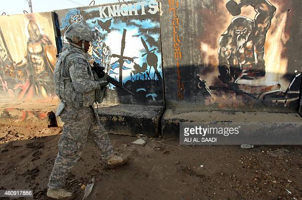 US soldier walks past graffiti painted on concrete blast walls at the Taji base complex which hosts Iraqi and US troops and is located thirty...