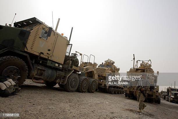 US soldier walks past US military lorries on July 23 at Contingency Operating Base Speicher on the outskirts of Tikrit 160 kilometres north of...