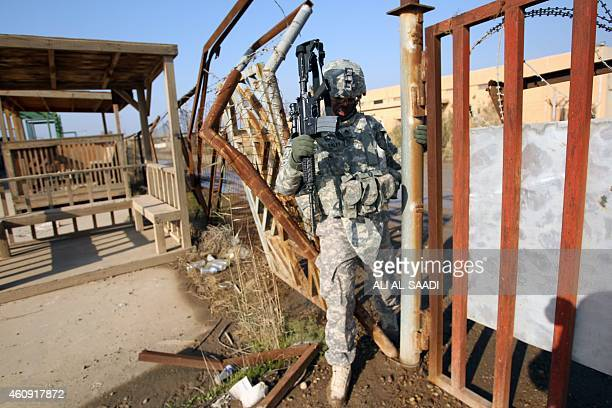 US soldier walks through a fence on December 29 2014 at the Taji base complex which hosts Iraqi and US troops and is located thirty kilometres north...