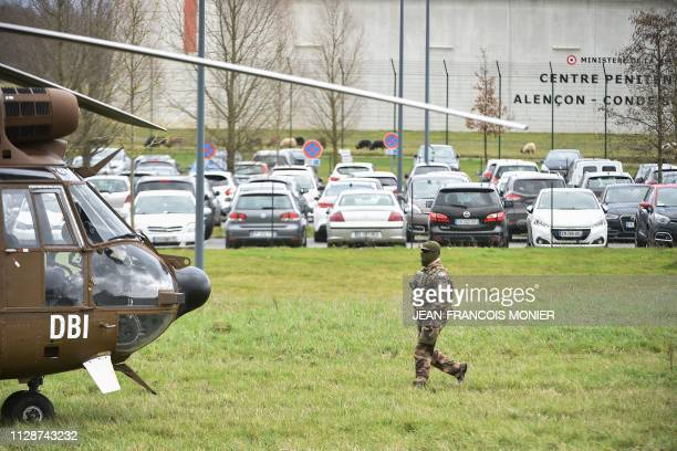 A soldier walks towards an army helicopter in front of the Penitentiary center of Alencon in CondesurSarthe western France on March 5 where a...