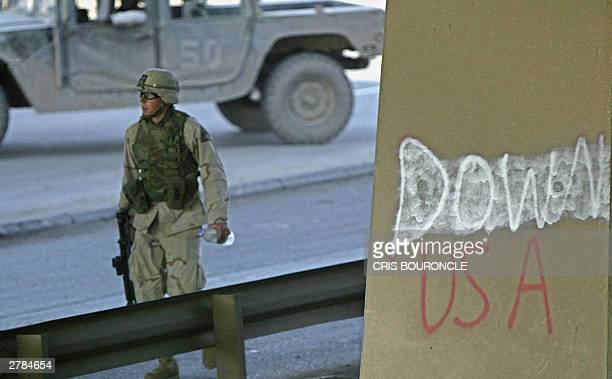 US soldier walks under a flyover bridge close to the site where a US military convoy came under attack 05 December 2003 in Baghadad Two bomb attacks...
