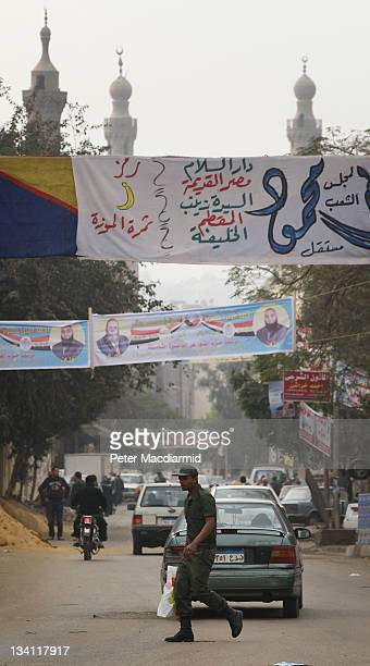 A soldier walks under election banners near the Citadel on November 26 2011 in Cairo Egypt Thousands of Egyptians are continuing to occupy Tahrir...