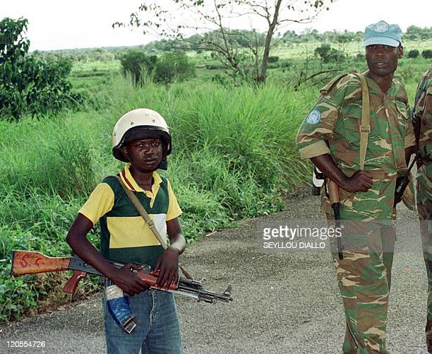 Soldier watches a well-armed young fighter of the United Revolutionary Front 30 August 2000 in Makot, 150 kilometres from the capital Freetown. A...