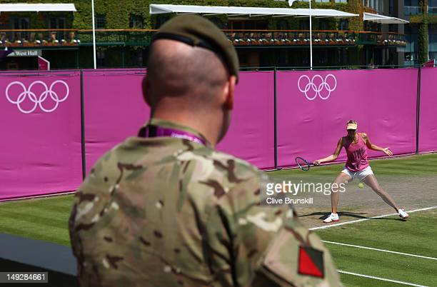 A soldier watches as Maria Sharapova of Russia practices during a practice session ahead of the 2012 London Olympic Games at the All England Lawn...