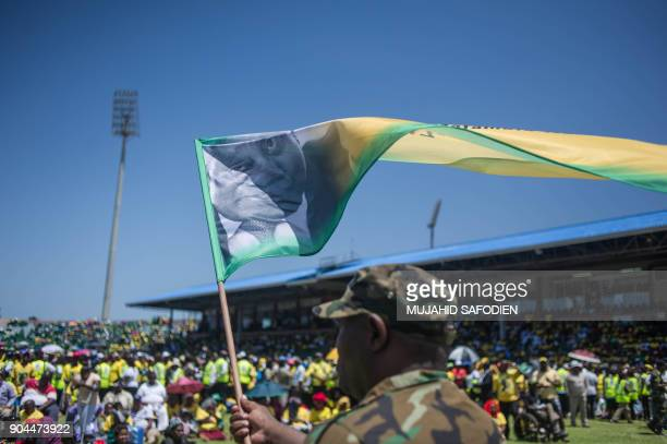 A soldier waves a flag bearing a portrait of ANC president Cyril Ramaphosa during the African National Congress' 106th anniversary celebration at...