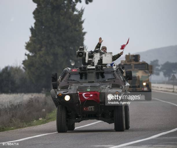 A soldier waves a Turkish flag as armoured military vehicles are being transported to support the units at border within the 'Operation Olive Branch'...