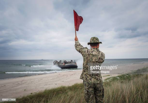 A soldier waves signal flags when a Landing Craft Air Cushion is driving to the beach during an Amphibious Landing Exercise on June 08 2017 in...