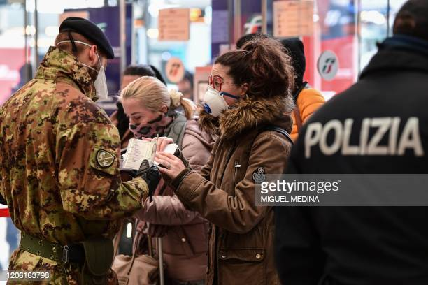 A soldier wearing a face mask controls the identification documents of passengers arriving at the Milan Centrale railway station on March 9 2020 as...