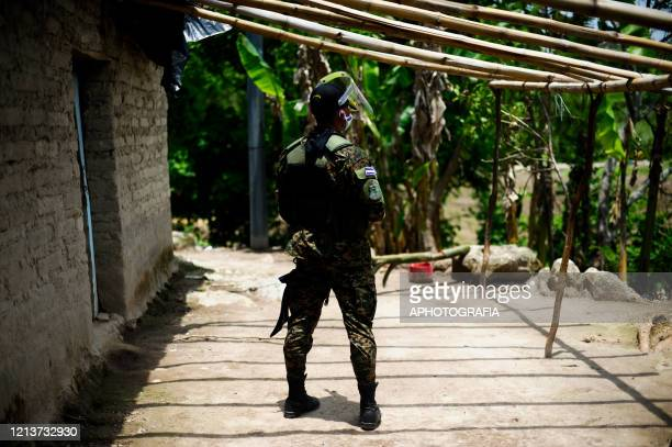 A soldier wearing a face mask patrols outside an adobe house to insure people comply with the government issued lockdown on May 18 2020 in Cuscatlan...