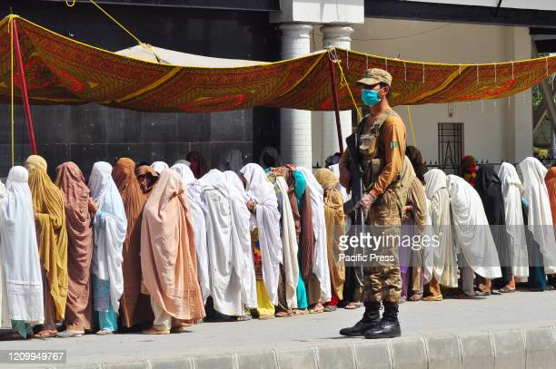 A soldier wearing a face mask stands on high alert on a road to avoid untoward incidents and maintain law and order situation while women queue to...