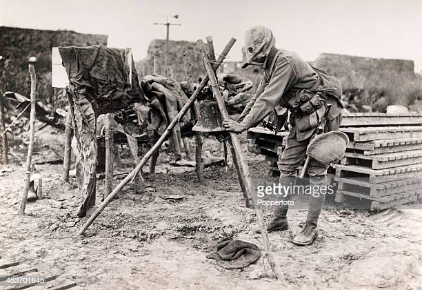 A soldier wearing a gas mask ringing a bell used to warn of a gas attack during World War One circa 1915