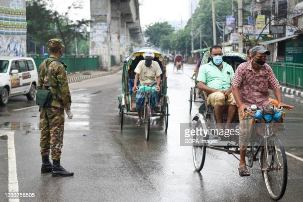 Soldier wearing a mask and gloves stands on guard along the road as part of a measure to stem the spread of the coronavirus pandemic. Bangladesh...