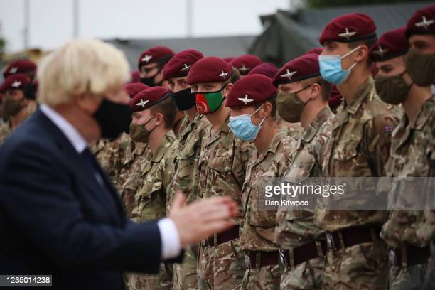Soldier wearing a protective face mask depicting the flag of Afghanistan looks on as UK prime minister Boris Johnson meets with military personnel...